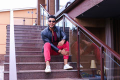 El musulmán masculino sienta la sonrisa y la presentación en las escaleras en restaurante encendido Imagen de archivo libre de regalías