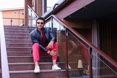El musulmán masculino sienta la sonrisa y la presentación en las escaleras en restaurante encendido Fotografía de archivo libre de regalías