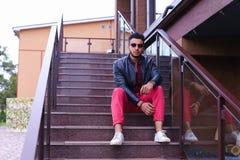 El musulmán masculino sienta la sonrisa y la presentación en las escaleras en restaurante encendido Fotografía de archivo