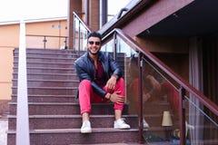 El musulmán masculino sienta la sonrisa y la presentación en las escaleras en restaurante encendido Imágenes de archivo libres de regalías