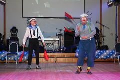 El número cómico del estallido del marinero con las banderas de señal realizado por los actores de imita el teatro y la payasada, Fotografía de archivo