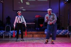 El número cómico del estallido del marinero con las banderas de señal realizado por los actores de imita el teatro y la payasada, Fotos de archivo libres de regalías