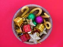 el número de oro 2018 y los ornamentos de la Navidad en una teca ruedan Imagen de archivo