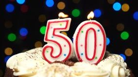 El número 50 encima de la torta - burning de la vela de cincuenta cumpleaños - sople hacia fuera en el extremo Fondo borroso colo almacen de video