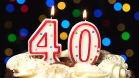 El número 40 encima de la torta - burning de la vela de cuarenta cumpleaños - sople hacia fuera en el extremo Fondo borroso color almacen de metraje de vídeo