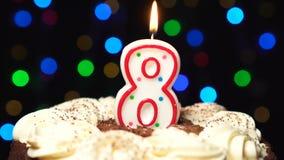 El número 8 encima de la torta - burning de la vela de ocho cumpleaños - sople hacia fuera en el extremo Fondo borroso color almacen de metraje de vídeo