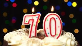 El número 70 encima de la torta - burning de la vela de setenta cumpleaños - sople hacia fuera en el extremo Fondo borroso color metrajes
