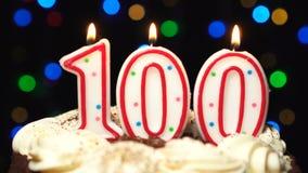 El número 100 encima de la torta - cientos burning de la vela del cumpleaños - sople hacia fuera en el extremo Fondo borroso colo almacen de metraje de vídeo