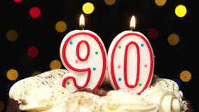 El número 90 encima de la torta - noventa burning de la vela del cumpleaños - sople hacia fuera en el extremo Fondo borroso color almacen de metraje de vídeo