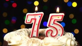 El número 75 encima de la torta - setenta y cinco burning de la vela del cumpleaños - sople hacia fuera en el extremo Fondo borro metrajes