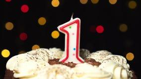 El número 1 encima de la torta - un burning de la vela del cumpleaños - sople hacia fuera en el extremo Fondo borroso color almacen de metraje de vídeo
