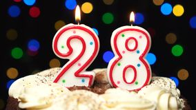 El número 28 encima de la torta - veintiocho burning de la vela del cumpleaños - sople hacia fuera en el extremo Fondo borroso co almacen de video