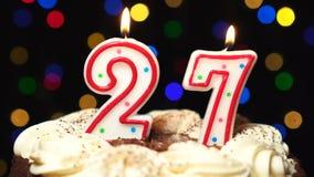 El número 27 encima de la torta - veintisiete burning de la vela del cumpleaños - sople hacia fuera en el extremo Fondo borroso c almacen de metraje de vídeo