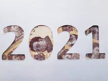el número 2021 formó con los billetes de banco mexicanos en el fondo blanco Fotos de archivo