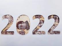el número 2022 formó con los billetes de banco mexicanos en el fondo blanco Foto de archivo