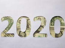 el número 2020 formó con los billetes de dólar en el fondo blanco Fotografía de archivo