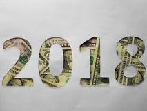 el número 2018 formó con los billetes de dólar en el fondo blanco fotografía de archivo