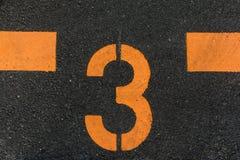 El número 3 impreso en el camino Imagen de archivo