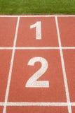 El número 1 y 2 en circuito de carreras en estadio de fútbol Foto de archivo