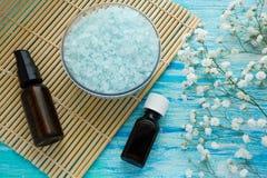 El Na embotella el baño herbario en una tabla de madera azul, balneario del aceite esencial y de la sal del mar con las flores Foto de archivo libre de regalías