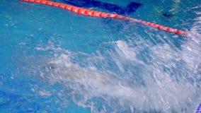 El nadador en el entrenamiento en la piscina realiza un giro de 180 grados metrajes