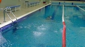 El nadador salta en piscina de los deportes metrajes