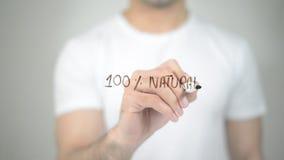 El 100% natural, escritura del hombre en la pantalla transparente fotos de archivo libres de regalías