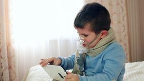 El nebulizador para la inhalación, niño con una máscara de oxígeno en su cara juega en la tableta, niño enfermo respira a través  almacen de video