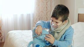 El nebulizador para la inhalación, niño enfermo respira a través del nebulizador, bebé hace la inhalación, muchacho con una másca almacen de video