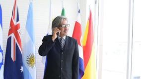 El negocio asiático o el hombre político con los vidrios del ojo utiliza el teléfono móvil para entrar en contacto con con el almacen de metraje de vídeo