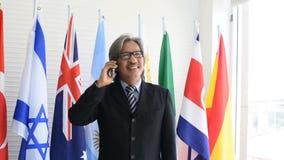 El negocio asiático o el hombre político con los vidrios del ojo utiliza el teléfono móvil para entrar en contacto con con el almacen de video