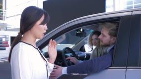 El negocio automovilístico, dependienta aconseja los pares jovenes de los clientes que se sientan en salón del coche mientras que almacen de video