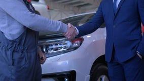 El negocio automovilístico, hombre del cliente pone llaves del coche en manos del mecánico de automóviles para la reparación en l almacen de metraje de vídeo