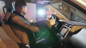El negocio automovilístico, hombre es se sienta detrás de la rueda del nuevo primer de la máquina en centro de ventas almacen de metraje de vídeo