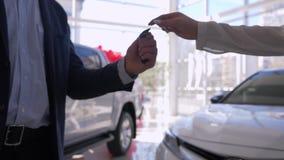 El negocio automovilístico, manos de la dependienta da llaves al dueño del cliente del coche y sacude el primer de las manos dura metrajes