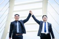 El negocio de dos asiáticos tiene victoria de la meta de negocio con la construcción de a imagenes de archivo