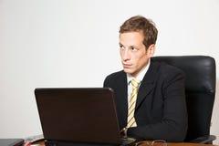 El negocio joven vistió al varón que se sentaba en su escritorio imágenes de archivo libres de regalías