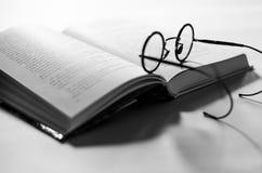 El negro alrededor de los vidrios viejos pone en un libro blanco abierto, que miente en un fondo blanco imágenes de archivo libres de regalías