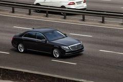 El negro de la clase de Mercedes S monta en el camino Contra un fondo de árboles borrosos imagen de archivo