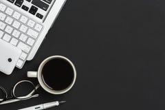 El negro de la tabla del escritorio de oficina con el ordenador, taza de café, founten la pluma, fotografía de archivo
