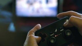 El negro del coj?n del juego que juega las manos del control del juego se cierra para arriba almacen de video