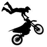El negro siluetea al jinete del motocrós en una motocicleta Imagen de archivo