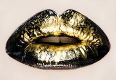 El negro y los labios del oro se cierran para arriba Fotos de archivo libres de regalías