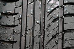El neumático de coche con con agua cae al fondo Fotos de archivo