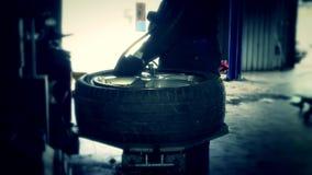 El neumático del montaje del reparador e infla el aire con el compresor eléctrico almacen de metraje de vídeo
