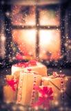 El nevar oscuro de la ventana rústica de la tabla de los regalos de la Navidad Imagen de archivo libre de regalías