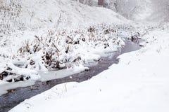 El nevar sobre un pequeño río Imágenes de archivo libres de regalías