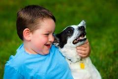El niño abraza cariñosamente su animal doméstico imagenes de archivo