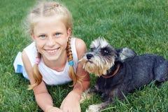 El niño abraza cariñosamente su perro casero, un schnauzer miniatura imagenes de archivo