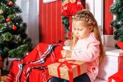 El niño abre un presente Año Nuevo del concepto, Feliz Navidad, ho Imagen de archivo